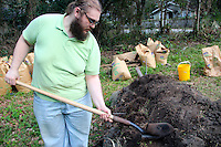 He shovels dirt onto a mound in a lot for urban gardening. He asked his landlord if it would be OK to use the empty lot on his block to grow food.