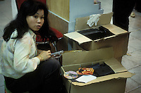 A woman packs pirated CDs into a box in Guangzhou, China.