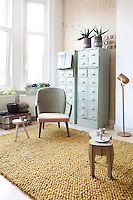 An alcove in the living room has been hung with brown paper. Teamed with a pair of old filing cabinets, this corner ties into the subtle brown, ochre and pale green/blue tones of the furnishings in the rest of the room