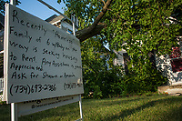 A sign declaring the plight of the family whose home was destroyed by a falling tree sits in front of the house on North State Street in Westerville, Ohio, three days after a storm felled trees and power lines leaving as many as 1 million people without power in Ohio. This house, occupied and for sale when the storm struck, is still waiting for an insurance adjuster to complete the damage claim although neighbors speculate the damage to be so severe that the house might not be repaired but torn down.