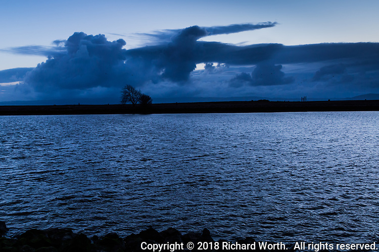 The clouds hovered over the rippling waters, and in those clouds appeared a giant eagle or hawk, a raptor, with  wings spread wide.