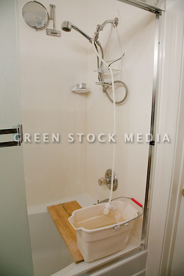 This shower has been retrofitted by its owner to recapture water while the water is heating up and during non-soap portions of the shower time. The recaptured wastewater (greywater) can be used for watering plants and gardens and even filling your toilet tank.