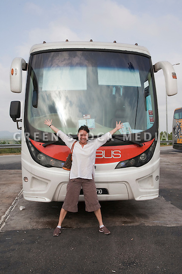 A mid adult woman excited about taking the bus from Kuala to Singapore. Kuala Lumpur, Selangor, Malaysia
