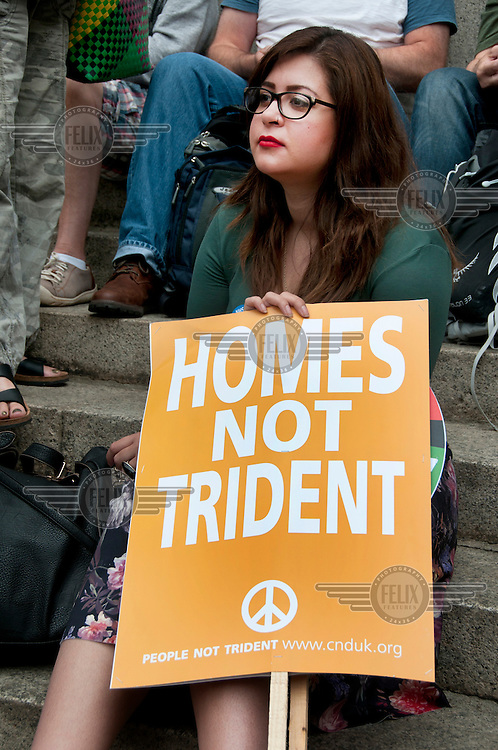 A woman holds a placard that reads: 'HOMES NOT TRIDENT' during the March Against Austerity in central London 20 June 2015.