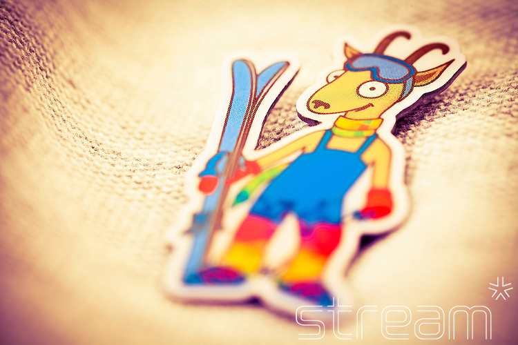 Deer skiing cartoon badge on white fabric.