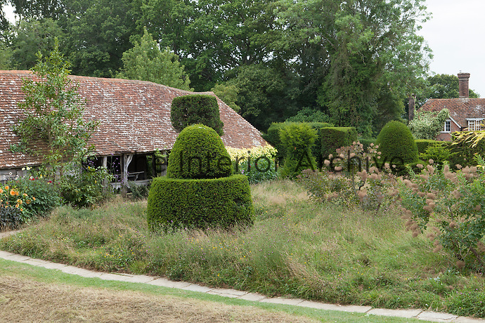 View across the topiary lawn at Great Dixter to 'The Hovel'
