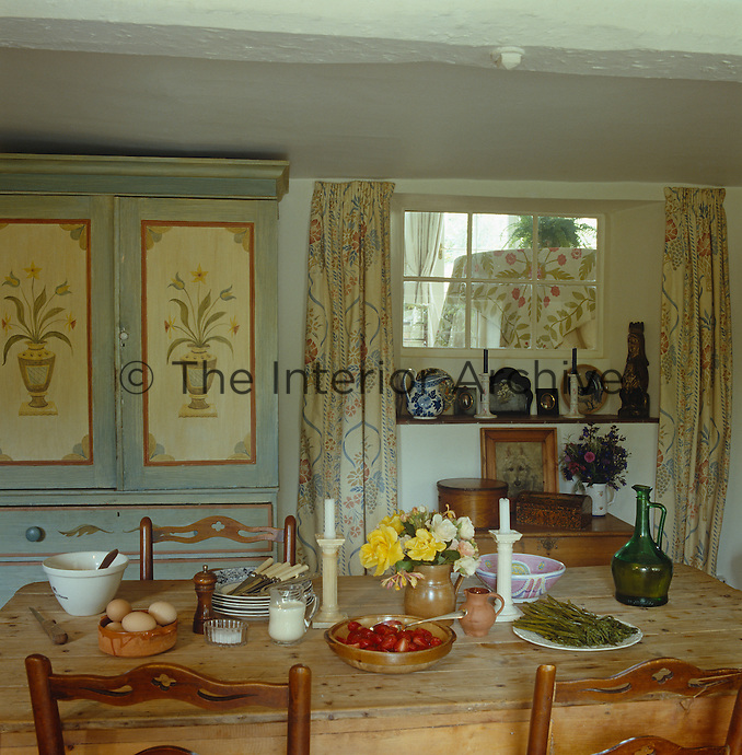 The scrubbed wooden table in the kitchen is set for an informal lunch