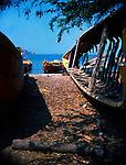 Old broken fishing boat beached on the sand with colourful painted fishing boats anchored to the shore, Santa Marta, Colombia. Circa 1975