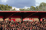 Home fans at Broadhurst Park, Manchester, the new home of FC United of Manchester during the second-half of the club's match against Benfica, champions of Portugal, which marked the official opening of their new stadium. FC United Manchester were formed in 2005 by fans disillusioned by the takeover of Manchester United by the Glazer family from America. The club gained several promotions and played in National League North in the 2015-16 season, but lost this match 1-0.