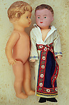 Innocent vintage female doll lying naked on antique paper next to boy doll wearing kimono and shoes