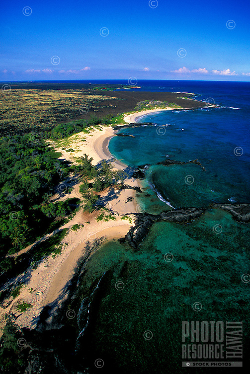 Aerial of Makalawena beach on the Big Island of Hawaii- clear blue ocean water and blue sky