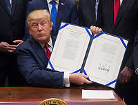 United States President Donald Trump holds up S. 544 the Veterans Choice Program Extension and Improvement Act after signing it in the Roosevelt Room at the White House in Washington, DC on April 19, 2017. Photo Credit: Molly Riley/CNP/AdMedia