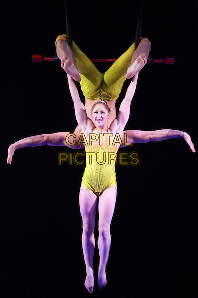Artists from Cirque Du Soleil ; Totem perform at the Royal Albert Hall, London, England..January 4th, 2012.stage performance circus costume show atmosphere gv general view full length performers balance balancing acrobat yellow trapeze .CAP/JEZ  .©Jez/Capital Pictures.