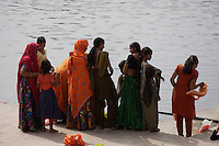 Women at lakeside wearing brightly coloured Sari`s during Pushkar Kartik Poornima festival. Ajmer district, Rajasthan, India