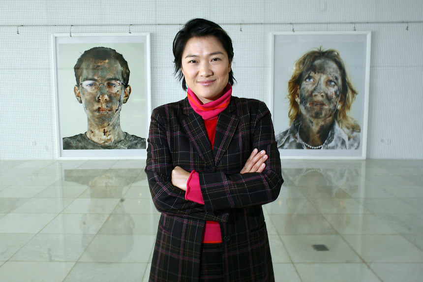 """Soho China Ltd. Co-CEO Zhang Xin poses in a gallery with photographs from a series called """"Survivor"""" in Beijing, China, on February 16, 2006. """"Even artists who have never exhibited abroad are beginning to demand prices of 1 million yuan,"""" said Zhang. """"These prices are unsustainable.""""."""