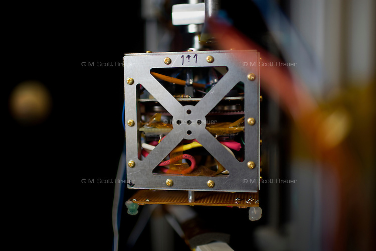A small satellite levitates in a vacuum chamber used to test thruster design in the Space Propulsion Lab at MIT.  Paulo Lozano is the Associate Director of the Space Propulsion Lab and an Associate Professor of Aeronautics and Astronautics at MIT in Cambridge, Massachusetts, USA.  Lozano's current research focuses on the development of small thrusters for satellites.  The thrusters his lab has developed are about the size of a single die cube and contain enough fuel to power the thrusters for a year in space.  The thrusters will be used on small satellites.