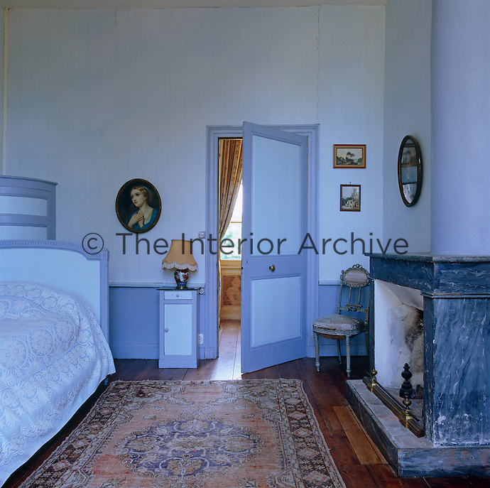 Another of the guest bedrooms is painted in Wedgwood colours with a 19th century French bed to match