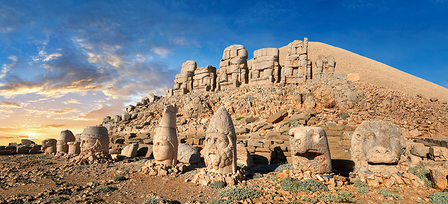 Statue heads at sunset with headless seated statues in front of the stone pyramid 62 BC Royal Tomb of King Antiochus I Theos of Commagene, east Terrace, Mount Nemrut or Nemrud Dagi summit, near Adıyaman, Turkey