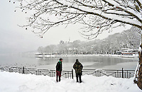 Pictured: Two walkers by the partially frozen over lake in Ioannina, Greece. Wednesday 11 January 2017<br /> Re: Heavy snow has affected the town of Ioannina, northern Greece