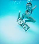 USA, Florida, St. Pete Beach, Girl (8-9) swimming in pool and reaching for one dollar banknote