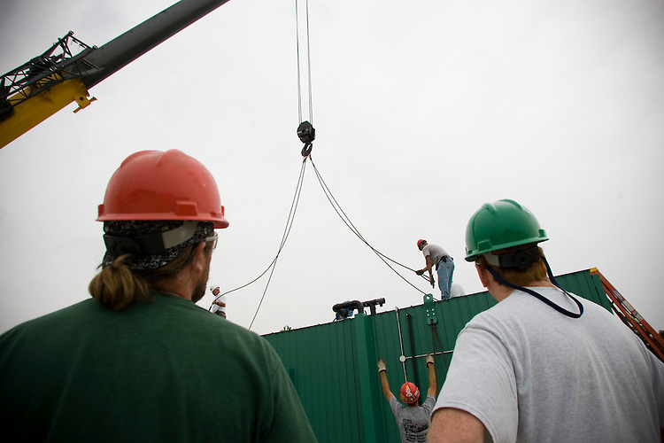 Workers attach the Wright Environmental in-vessel composting unit to a crane that will lower the unit into the future Ohio University compost site on Dairy Lane. Photo By: Josh Armstrong