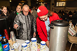 WATERBURY, CT. 21 December 2019-122119BS290 - Cruz Rivera, left, and Laura Dennis, right, get some hot coffee, prior to a Christmas Party for the less fortunate and homeless in the basement of the Basilica of Immaculate Conception on Saturday. Bill Shettle Republican-American