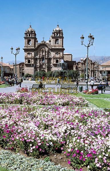 Looking across Plaza de Armas to Iglesia La Compania de Jesus, and fountain, Cusco, Peru
