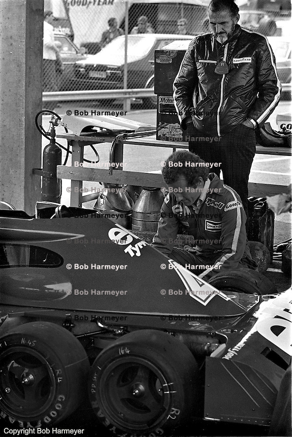Don Nichols (standing), owner of the Shadow Formula 1 team, studies the Tyrrell P34 six-wheel Formula 1 car during practice for the 1976 Grand Prix of Sweden at Anderstorp.