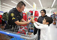 NWA Democrat-Gazette/DAVID GOTTSCHALK Detective Fredy Villeda (from left), with the Springdale Police Department, and Crystal Galvan, a sophomore at Springdale High School and member of the Law and Public Safety Academy shop Tuesday, December 4, 2018, with Manuel Berrocal, 6, at the Walmart Supercenter on Pleasant Street in Springdale. More than 200 children participated in the Springdale Police Department Shop with a Cop program. The department collected $45,000 this year for the program.
