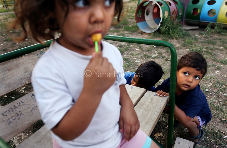 A little girl sucks a lollipop under the hungry gaze of a little friend at the Dom Maika i Dete (Home for Mother and Child) adoption home in Vidin, Bulgaria on August 31, 2008.<br /> <br /> Children for adoption in Vidin, Bulgaria, live here. The home's director, Maria Rangelova, describes that two decades ago, the home carried more than double the children, who were mostly given away because they were born out of wedlock. While the number of children has decreasted from about 180 to 80 from waning birth rates and shifting cultural perceptions of birth outside of marriage, there remain many kids in need of adoption. Now, she says, most parents who give their children away do so because of financial want -- one that robs them of the ability to support their kids, or leaves them unable to cure an illness that has incapacitated them as caregivers. The home often struggles to provide an adequate amount of toys, snacks and personnel necessary for the children's caregiving.
