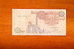 Egyptian one pound currency note on table with Arabic script and mosque