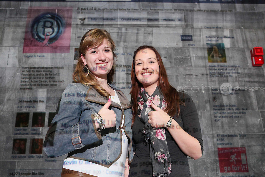 NO Repro Fee.27/10/2010.  Ballygowan Pink's B Part Of It campaign in support of Breast Cancer Awareness Month. Hundreds of UCD students got behind Ballygowan Pink's B Part Of It campaign in support of Breast Cancer Awareness Month. Pictured are  Anne Hanschot and Ciara Galvin from Mayo who posted messages of support to the life-sized Facebook Wall which was projected onto the entrance of UCD library. A live stream of students' messages was seen throughout the day to raise awareness of breast cancer and support the Marie Keating Foundation. Picture James Horan/Collins Photos