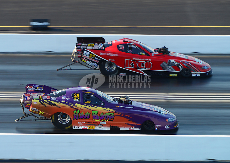 Jul. 1, 2012; Joliet, IL, USA: NHRA  top alcohol funny car driver Cassie Simonton (near lane) races alongside Mickey Ferro during the Route 66 Nationals at Route 66 Raceway. Mandatory Credit: Mark J. Rebilas-