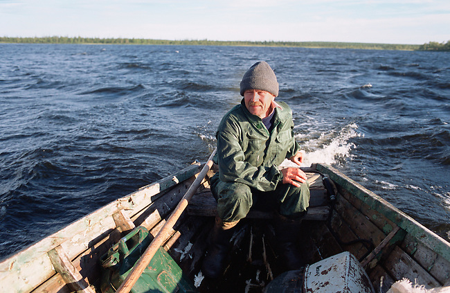 Sasha, a Sami man, stears his boat back to camp after checking his fishing nets near Lovozero (Strong Lake. Kola Peninsula, NW Russia