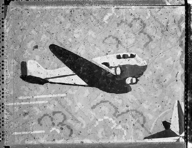 4x5 Black & White Polaroid of old cracked flooring material. The design shows an old reto art deco style airplane.
