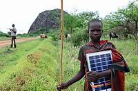 UGANDA, Karamoja, Kotido, karamojong pastoral tribe, young shepherd with grazing cattle carrying a solar panel to charge the mobile phone /Karamojong Ethnie, junger Hirte mit Vieh beim Weiden, Junge mit Solarpanel zum Aufladen des Handy