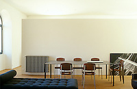 The living-dining area is furnished with a long steel dining table surrounded by plywood chairs and a large black-and-white photographic print is propped casually against a wall