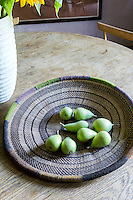 Green pears on a woven dish.