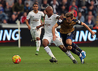 (L-R) Andre Ayew of Swansea is challenged by Nacho Monreal of Arsenal during the Barclays Premier League match between Swansea City and Arsenal at the Liberty Stadium, Swansea on October 31st 2015