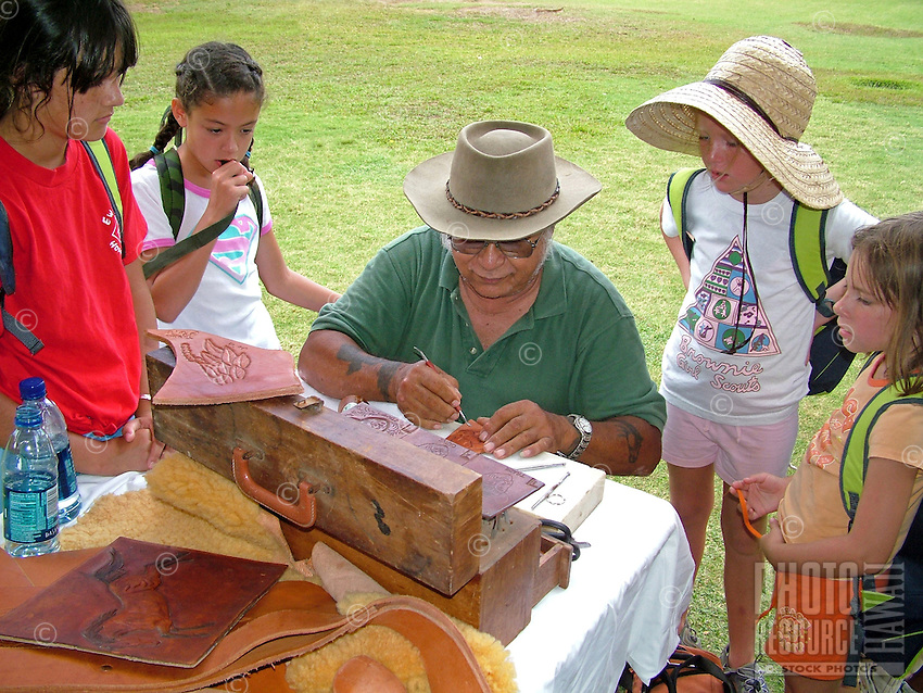 Craftsman demonstrating to school children how he carves a design in leather.