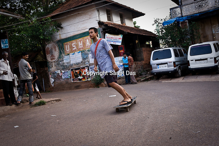 """Daruka Dasa of the Kaliya Mardana Krishna Ashram is seen using the skate-board in the local market of coastal town of Mulki, just north of Mangalore, Karnataka, India.  ..Krishna devotees in the Gaudiya Vaishnava tradition of Hinduism, they are known collectively as the """"surfing swamis."""" The """"surfing ashram"""" is growing in popularity and surfing here is a form of meditation, a spiritual practice leading to heightened states of awareness."""