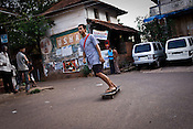 "Daruka Dasa of the Kaliya Mardana Krishna Ashram is seen using the skate-board in the local market of coastal town of Mulki, just north of Mangalore, Karnataka, India.  ..Krishna devotees in the Gaudiya Vaishnava tradition of Hinduism, they are known collectively as the ""surfing swamis."" The ""surfing ashram"" is growing in popularity and surfing here is a form of meditation, a spiritual practice leading to heightened states of awareness."
