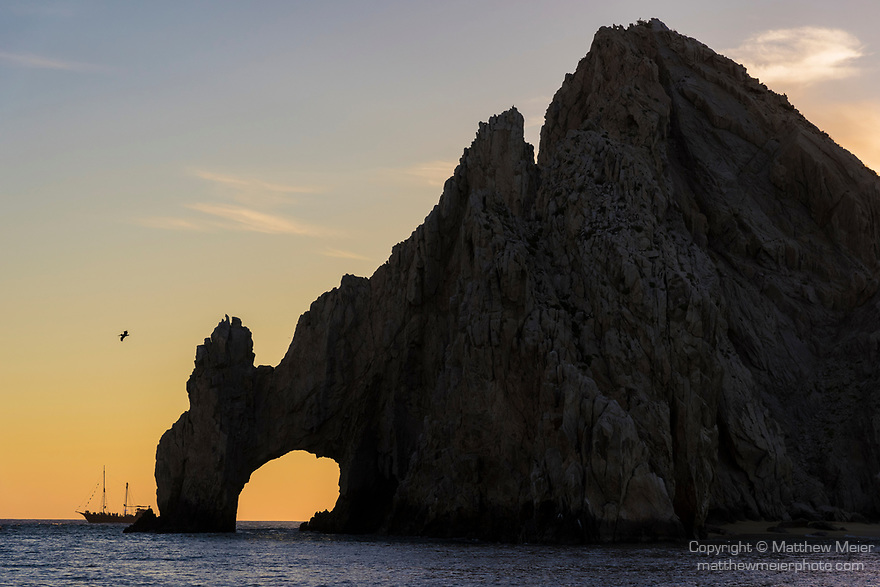 Sea of Cortez, Cabo San Lucas, Mexico; the Arch of Cabo San Lucas and a wooden pirates ship are silhouette against a sunset sky, these rocks at the southern most end of the Baja Peninsula separate the Sea of Cortez from the Pacific Ocean