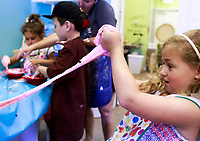 NWA Democrat-Gazette/CHARLIE KAIJO Brynn Sager, 7, of Rogers plays with slime she made during a summer art workshop, Thursday, July 5, 2018 at Imagine Studios in Rogers. <br /><br />Imagine Studios will host nine weeks of summer art camps and workshops, each with different themes. Activities include canvas painting, pottery painting, slime making and water color painting.