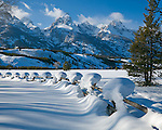 Grand Teton National Park, WY <br /> Snow capped fence line with the peaks of the Teton range in winter light