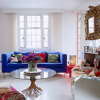 A bright blue sofa and mirrored chair stand out against the all white walls of the living room