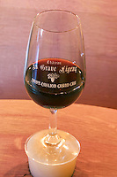 A glass of red wine on the silicon bung plug on the barrel - Chateau La Grave Figeac, Saint Emilion, Bordeaux