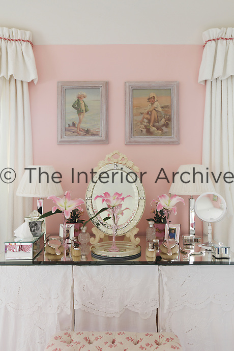 A glass topped dressing table with white embroidered table cloths in a pink bedroom
