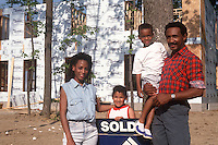 Proud family stands with sold sign at site of home construction