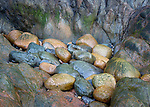 Acadia National Park, Maine: Colorful rocks piled against cliff face at Hunters Beach